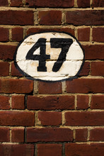 Hand-painted Decorative House Number On A Brick Wall – 47 (forty-seven)