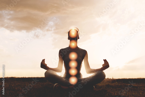 Valokuva  Woman practicing meditation in sunset, with chakras marked