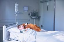 Boy Patient In Bed Hugging Teddy Bear On Hospital Children's Ward