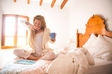 Young Woman Using Digital Tablet Yawning In Bed In Morning