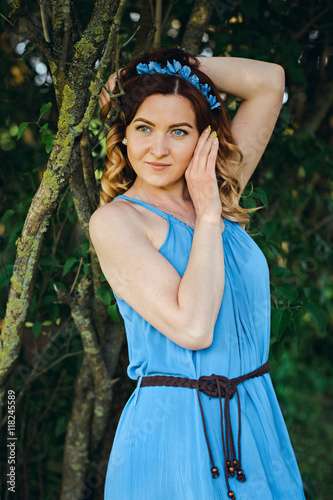 Keuken foto achterwand Gypsy Old fashion portrait of a beautiful elegant red-haired woman dressed in a blue dress and a wreath of flowers posing in a windy Sunny day in a summer outfit, in nature. European city