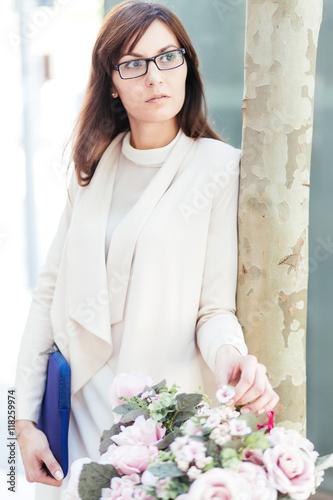 Elegant businesswoman in beige suit touching decorative flowers in the street