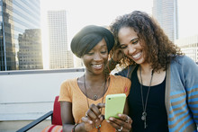 Women Using Cell Phone Togethe...