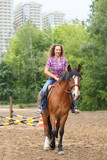 Fototapeta Konie - Happy woman with curly hair riding a horse in park near the apartment complex