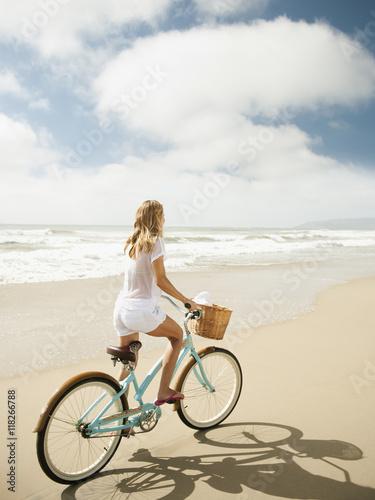 Fototapeta Caucasian woman riding bicycle on beach obraz na płótnie