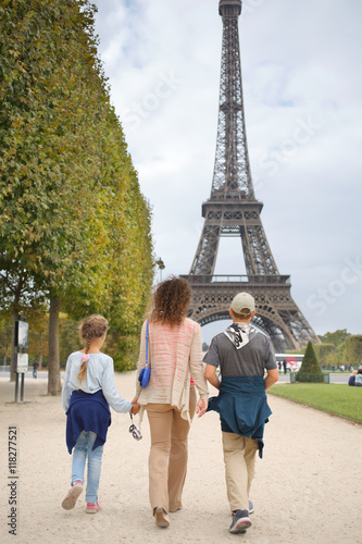 Fototapeta Mother, son and daughter walk in the park near the Eiffel Tower in Paris, view from the back obraz na płótnie