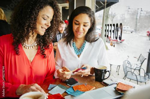 Tuinposter Stof Businesswomen examining fabric samples in cafe