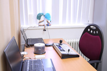 Desk With Two Laptop Computers And Remote Control Near A Window With Shutters