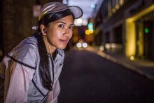 Asian Runner Resting On City Street At Night