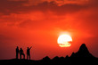 canvas print picture - Landscape with silhouette of standing people and beautiful sky with big sun. Friends on the high mountain peak against the beautiful sunset. High rocks. Travel, Climbing, Trekking.