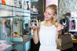 Young cheerful woman picking fashion earrings