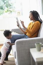 Black Woman Using Digital Tablet On Sofa Near Baby Daughter