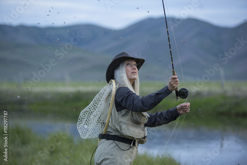 Papiers peints Peche Caucasian woman casting fishing line in remote lake