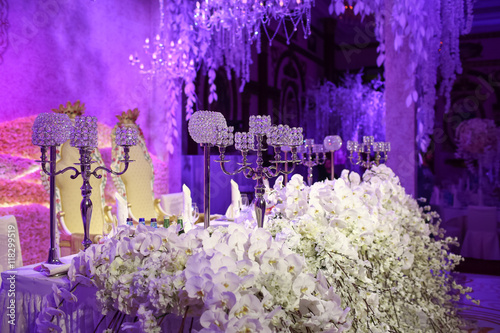 Poster Violet Beautiful restaurant interior table decoration for wedding. Flower . White orchids and sakura in vases. Candles.