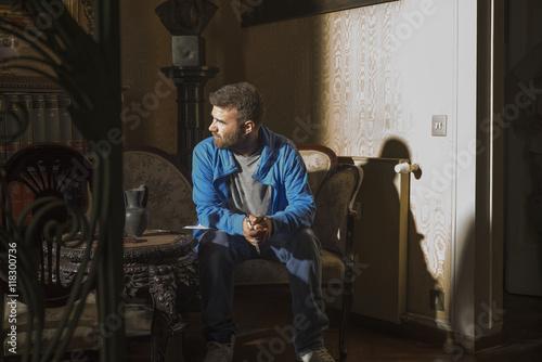 Caucasian man sitting in sunlight in living room