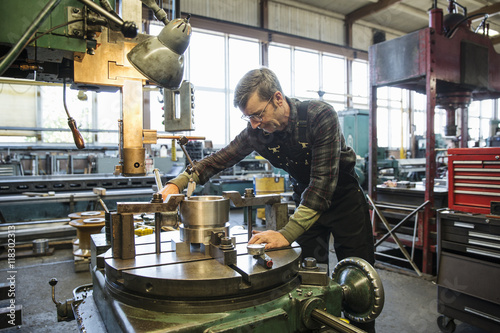 Caucasian man using machinery in metal shop