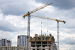 Construction of multi-storey buildings with Cranes. Workers work