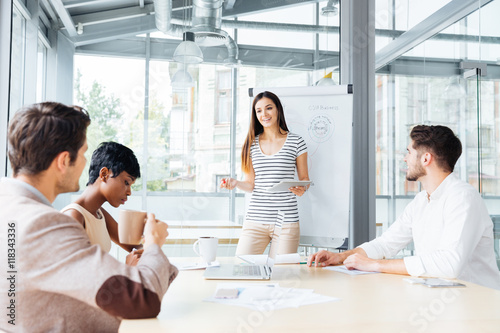 Fotografie, Obraz  Smiling woman making presentation for business people in office