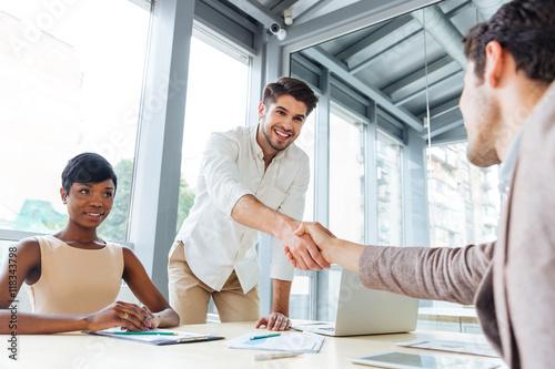 Fotografie, Obraz  Businessmen shaking hands and ending business meeting in office