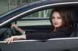 Young confident businesswoman driving car