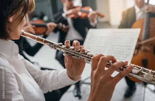 Photo Flutist playing her instrument on stage