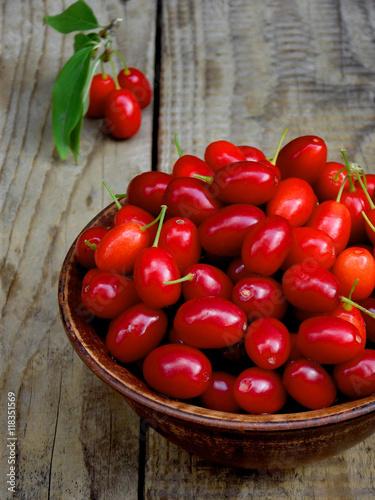 Valokuva  dogwood (cornelian cherry berry) in bowl on wooden background