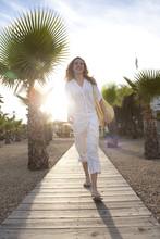 Woman Walking On Wooden Boardwalk In Park