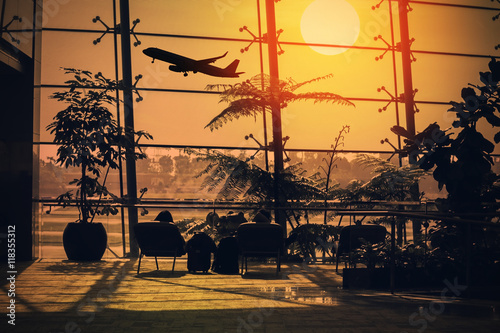 Poster Aeroport Tourists relax on the hammock in the lounge in the airport waiting to board a plane with a beautiful sunset and the plane background.