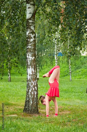 Foto op Aluminium Gymnastiek Young beautiful preteen girl doing gymnastics outdoors