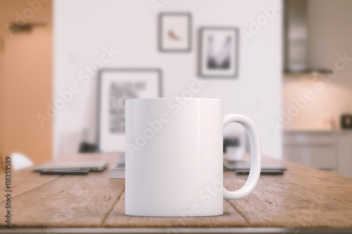 White blank coffee mug on a kitchen table with laptops in the background, ready for your custom design/quote.
