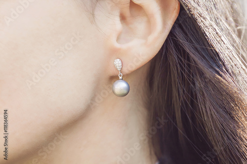 Woman ear wearing beautiful luxury earring Fototapeta