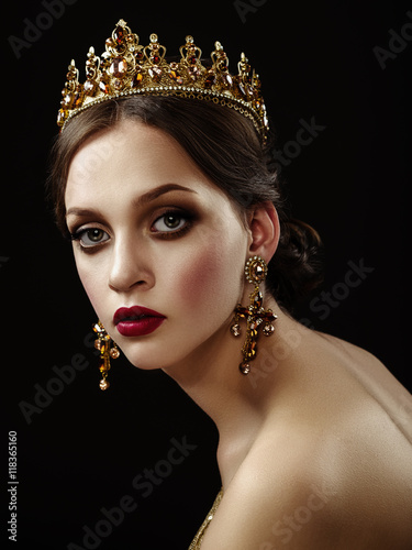 Fényképezés  Beautiful brunette girl with a golden crown, earrings and profes