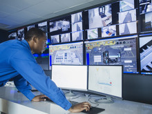 Black Security Officer Watching Surveillance Cameras