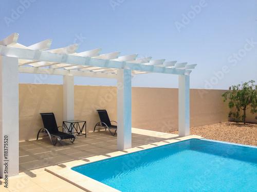 Fotografia  White poolside pergola, gazebo providing shade on a terrace patio area next to a swimming pool
