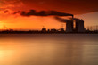 Coal Power Plant on a Lake at Sunrise, Exhaust Fumes blown by Storm, long exposure