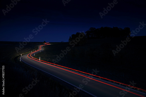 Valokuva  Car Driving Down a Winding Country Road, long exposure, Taillights in blurred mo