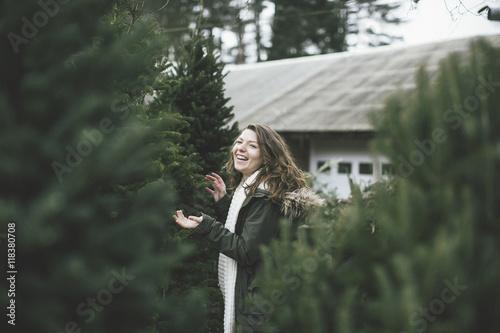 Caucasian woman walking in Christmas tree lot