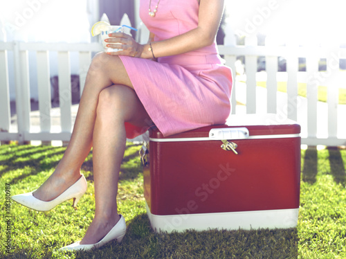 Glamorous woman sitting on vintage cooler in backyard