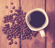 top view on cup of coffee over grunge wooden bacgkround.,vintage tone