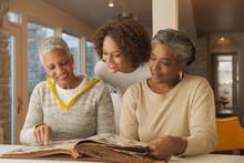 Women Looking At Family Photo Album