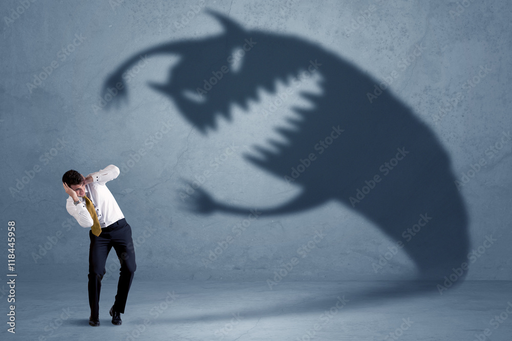Fototapeta Business man afraid of his own shadow monster concept
