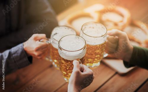 close up of hands with beer mugs at bar or pub Wallpaper Mural