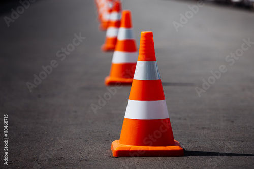 Fotografie, Obraz  bright orange traffic cones standing in a row on dark asphalt