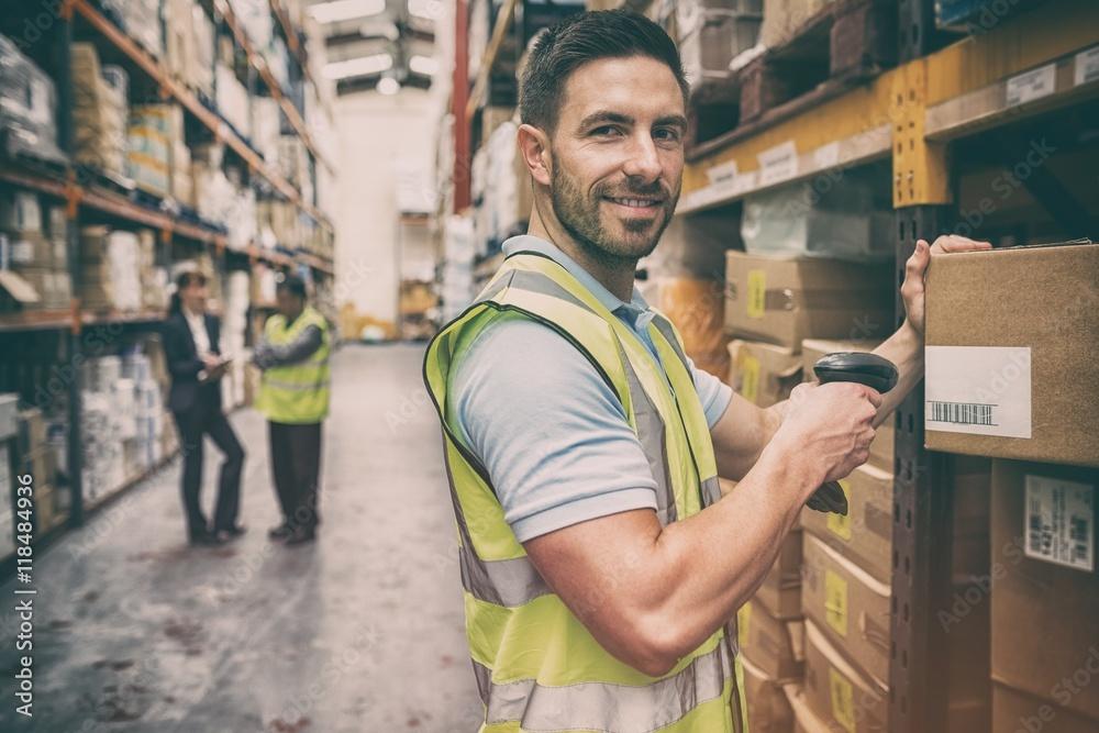 Fototapeta Warehouse worker scanning box while smiling at camera