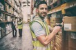 canvas print picture - Warehouse worker scanning box while smiling at camera