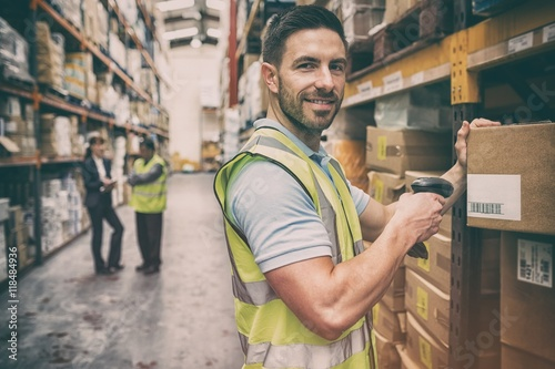 Vászonkép Warehouse worker scanning box while smiling at camera