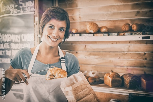 Foto op Plexiglas Bakkerij Pretty waitress picking up croissant