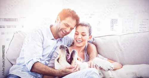 Fotografie, Obraz  Happy couple petting their yellow labrador on the couch