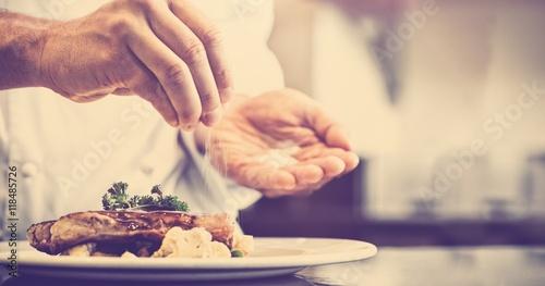 Fototapeta Closeup mid section of a chef putting salt obraz