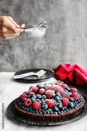 Fotografía  Female hand decorating chocolate tart with berries on black plate